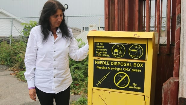 Christine Porter, the director of Ally Centre, stands beside a needle kiosk.