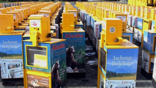 Hundreds of old newspaper sales boxes are shown Monday, Sept. 11, 2017, in a vacant lot near the former offices of the Alaska Dispatch News in Anchorage, Alaska.