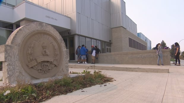 Students stand outside the doors of mâmawêyatitân centre, home of the new Scott Collegiate High School.