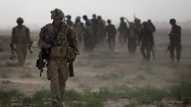 A Canadian soldier carries his weapons after a mission southwest of Kandahar, Afghanistan, in 2010. The Canadian government wants to build a memorial to Canada's 12-year mission in the country in Ottawa.