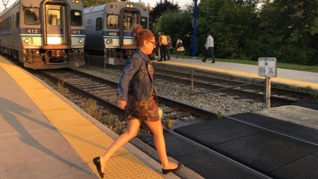 A commuter crosses the tracks at Roxboro-Pierrefonds station early Wednesday morning. A 17-year-old girl was critically injured while crossing there Tuesday. Police say she was wearing headphones at the time.
