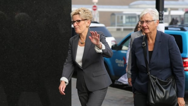 Ontario Premier Kathleen Wynne waves to reporters as she heads to court to testify at the trial of two Liberals accused of bribery in the 2015 Sudbury byelection.