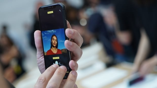 An Apple employee demonstrates Portrait Lighting on an iPhone X inside the Steve Jobs Theatre at Apple Park in Cupertino, Calif. The new feature uses facial recognition and augmented reality technologies to simulate different types of lighting on a person's face.