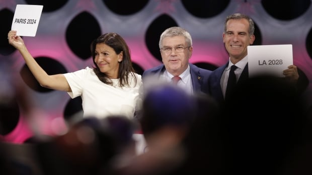 International Olympic Committee president Thomas Bach stands between Paris mayor Anne Hidalgo, left, and Los Angeles mayor Eric Garrett at the end of the IOC session in Lima, Peru, on Wednesday. The committee voted to ratify Paris as the host city of the 2024 Games and L.A. for 2028.