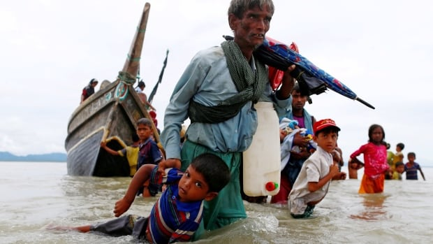 Rohingya refugees walk to the shore after crossing the Bangladesh-Myanmar border by boat through the Bay of Bengal in Shah Porir Dwip, Bangladesh, on Sept. 10.