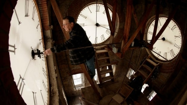 A technician changes the time on large clocks. Alberta is considering ending the twice-yearly ritual of springing ahead and falling back.