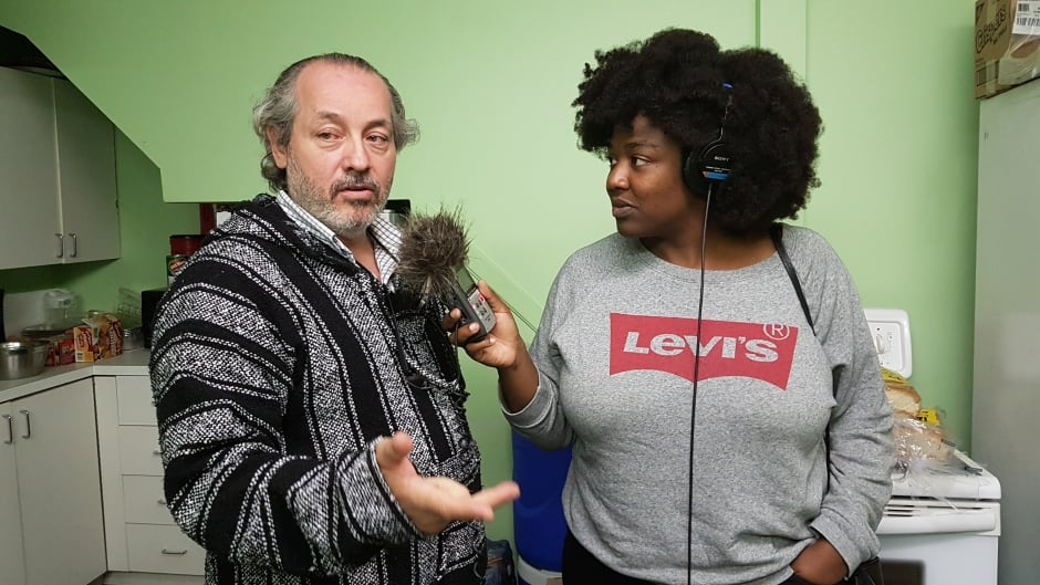 Michel Monette gives Now or Never host Ify Chiwetelu a tour of Coalition d'aide aux Refugies à Montreal.