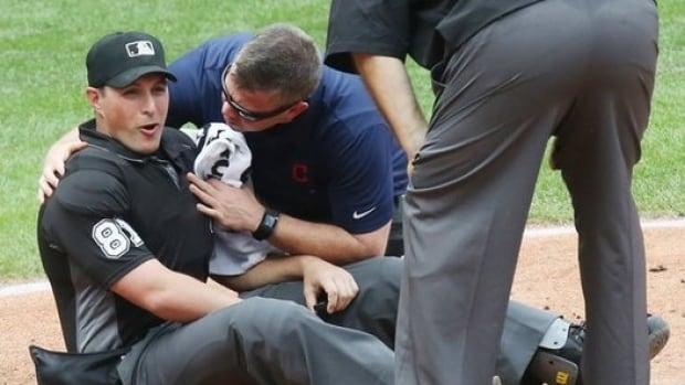 Umpire Quinn Wolcott is tended to after being knocked down by a Buck Farmer fastball. Friday, MLB ruled there was no intent by Farmer on the play.