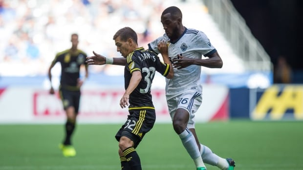 Tony Tchani, right, of the Whitecaps vies for the ball against Pedro Santos of the Crew during Vancouver's 2-2 draw on Saturday.
