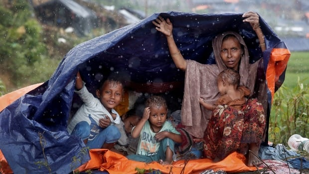 Rohingya refugees shelter from the rain in a camp in Cox's Bazar, Bangladesh.