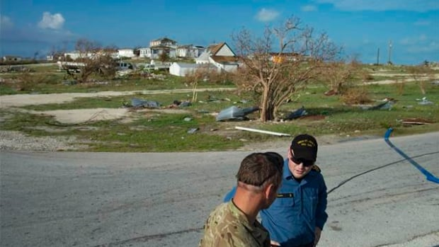 A crew member from HMCS St. John's consults with a British Royal Marine during a humanitarian aid mission on South Caicos island following Hurricane Irma's strike.