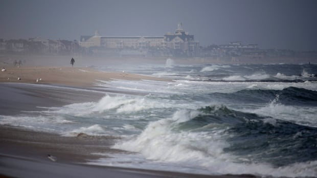 A beach-goer walks along the water as waves crash in Manasquan, N.J., last Thursday. Swells are up from recent hurricanes in the Atlantic Ocean, including Hurricane Jose, which is expected to stay out at sea.