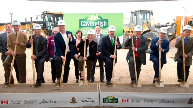 Cavendish Farms president Robert K. Irving, centre right, flanked by provincial and municipal leaders, breaks ground on a new potato-processing facility in Lethbridge, Alta.
