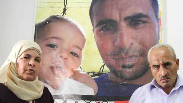 The parents of Mohammad Abu Shahin stand in front of a poster of the 32-year-old, who was convicted of killing Danny Gonen, in their home in the Qalandia refugee camp.