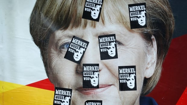 An election campaign poster in Frankfurt shows Angela Merkel, top candidate of the Christian Democratic Party (CDU), stickered with badges reading 'Merkel must go.'