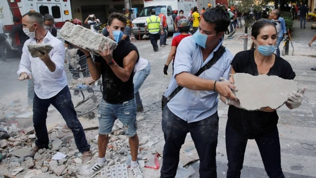 People remove debris outside a collapsed building after an 7.1 magnitude earthquake in Mexico City, Mexico Sept. 19, 2017.