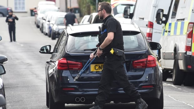 A police officer carries bolt cutters outside a house that was searched Wednesday in connection with a flashbomb that went off in the London tube.