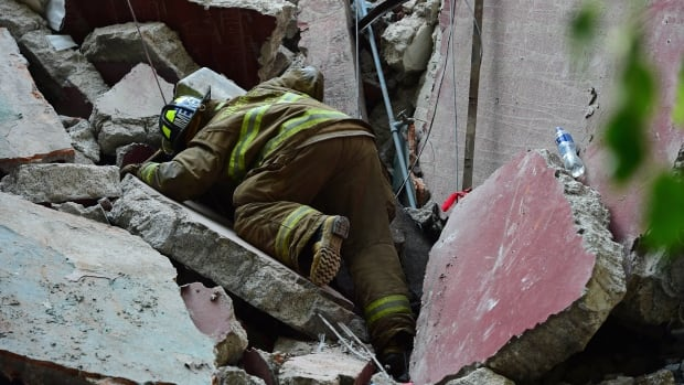 A firefighter searches for survivors among the debris from a flattened building after a powerful quake in Mexico City on Sept. 19, 2017.
