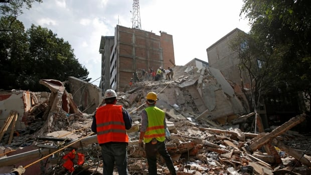 Rescuers watch fellow workers search for people under the rubble of a collapsed building after an earthquake hit Mexico City on Sept. 19, 2017.
