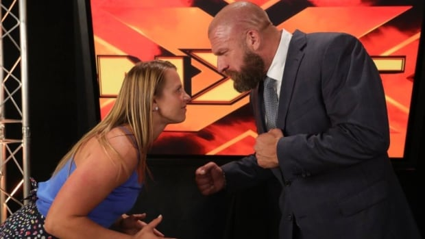 Canadian freestyle wrestler Erica Wiebe, left, poses with executive vice president of Talent, Live Events & Creative for WWE Paul Triple H Levesque at a taping in Florida.