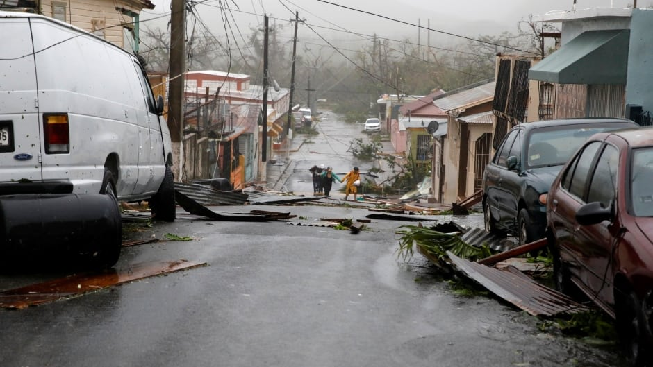 People walk on the street next to debris after the area was hit by Hurricane Maria in Guayama, Puerto Rico.