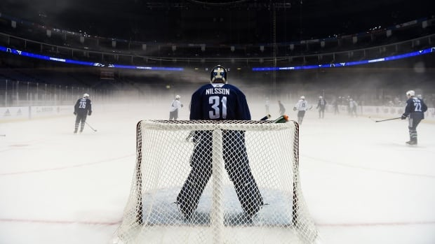 Vancouver Canucks' goaltender Andres Nilsson guards his post at the foggy Mercedes-Benz arena during Canucks practice, ahead of Thursday's pre-season game against the Los Angeles Kings in Shanghai.