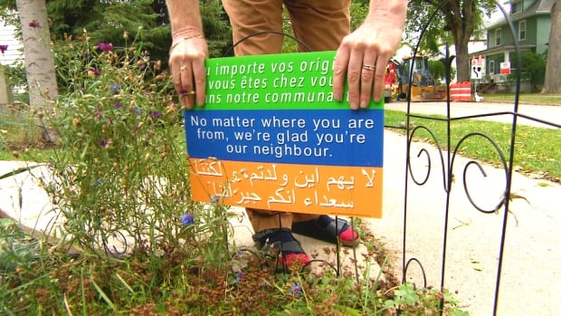 A Winnipeg woman has begun selling lawn signs with a welcoming message for newcomers as a fundraiser for the Manitoba Interfaith Immigration Council.