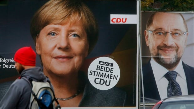 A man walks by election posters of German Chancellor Angela Merkel, left, and her challenger Martin Schulz from the Social Democrats. German elections will be held on Sunday.