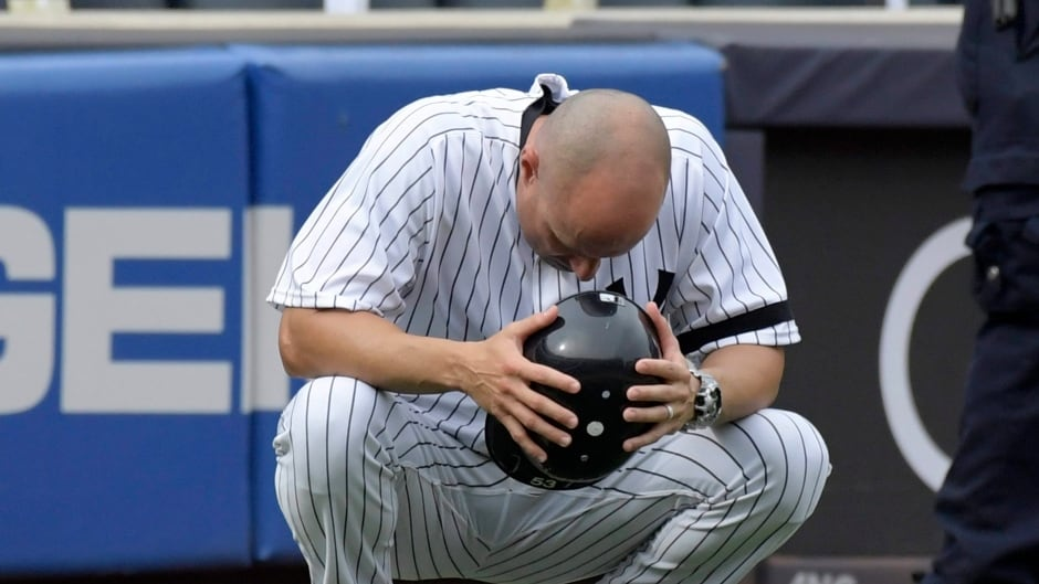 New York Yankees third base coach Joe Espada holds his helmet after a young girl was hit by a line drive during the fifth inning.