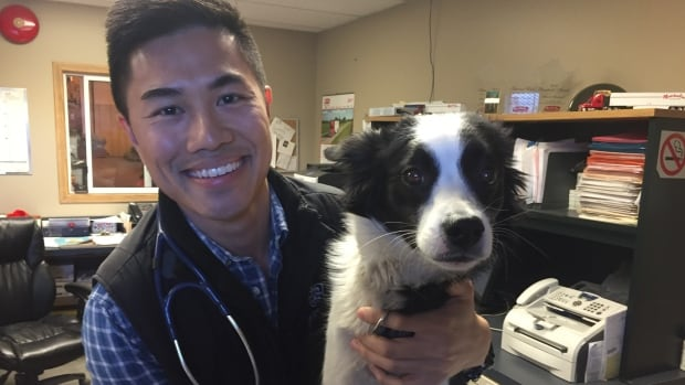 Chris Lam, Inuvik's accidental veterinarian, poses with Bella the border collie cross.
