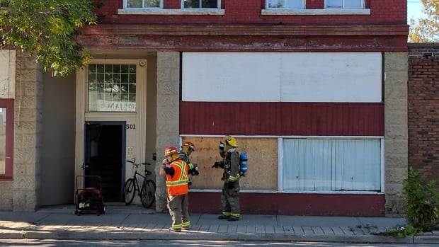 Firefighters stand outside a Simpson Street apartment building after extinguishing a fire in one of the units' kitchens on Thursday afternoon.