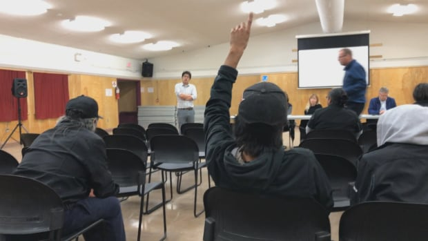 A community member raises his hand for a question at a legalized cannabis information session in Behchoko, N.W.T., Wednesday evening.