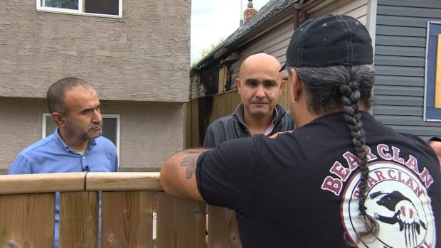 Mannan Hamrasho, left, says he was beaten and robbed earlier this year. He woke up Tuesday to find hateful graffiti on his fence. Nour Ali, an interpreter and member of the Kurdish Initiative for Refugees (right), then called 911 and the Bear Clan has since stepped in to help.