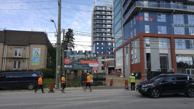 """A photo of TheHub from Columbia Street. The sign advertising the units says """"guaranteed move-in August 2017."""""""
