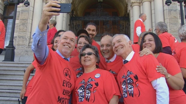 John Horgan leads an Orange Shirt Day selfie with Phyllis Webstad (centre), Indigenous relations minister Scott Fraser, and several other MLA's on the steps of the B.C. legislature