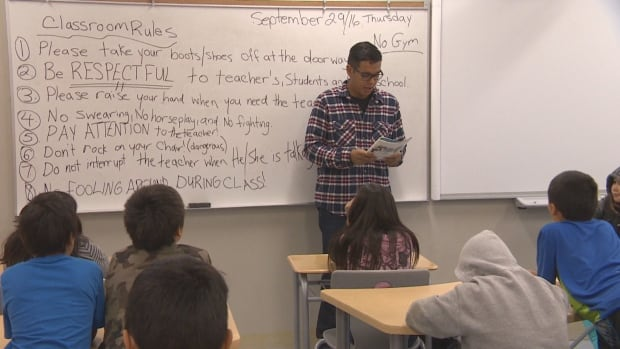 A teacher's assistant reads to students in Shamattawa First Nation. The community is short about 11 teachers, leaving 200 kids out of school. But it's not the only Manitoba First Nation affected by teacher shortages.