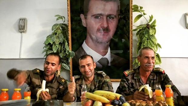 Under the gaze of their president, Bashar al-Assad, Syrian army officers host a lunch for visiting journalists.