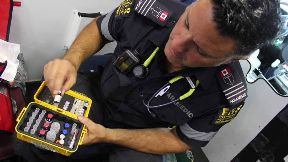 Toronto paramedic Jason Benaim pulls a vial of naloxone out of a drug kit in the back of an ambulance.