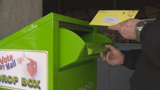 A St. John's municipal election voter drops a mail-in ballot at a box placed outside city hall in St. John's.