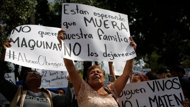 Family members holding signs that read in Spanish 'They are Waiting for our Family to Die,' 'They are Still Alive. Don't Kill Them' and 'No Heavy Machinery,' protest outside a quake-collapsed seven-storey building in Mexico City's Roma Norte neighbourhood on Friday.