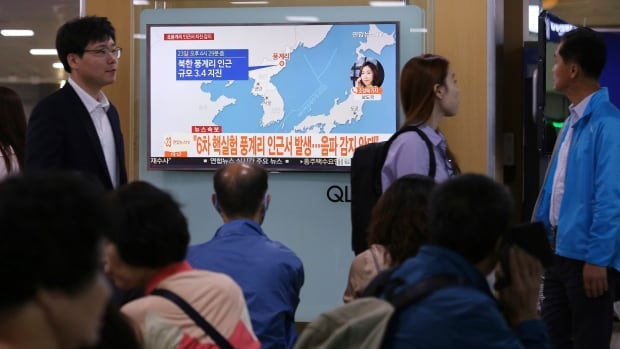 People in Seoul watch a TV news report Saturday on a mysterious earthquake in North Korea that stoked concerns it might have been caused by human activity. South Korea's weather agency said it assessed the quake as natural but seismologists in China saw the likely cause as an explosion.