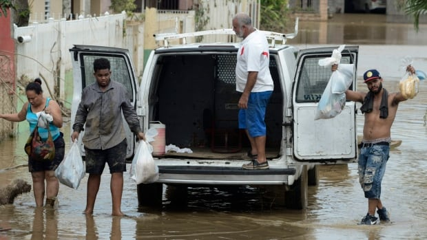 Residents manage provisions on Friday after Hurricane Maria passed through Puerto Rico. Because of the heavy rains brought by Maria, thousands of people are being told to move from a part of the territory that could face catastrophic flooding from a failing dam.
