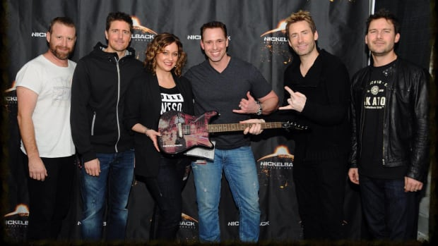 Saskatoon city councillor Troy Davies (centre) has a wall in his basement dedicated to Nickelback souvenirs, including a signed guitar.