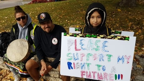 A child at Saturday's Rally for Indigenous Rights hold a sign saying 'Please support my right to a f