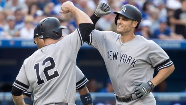 New York Yankees' Greg Bird, right, celebrates at home plate with teammate Chase Headley after hitting a three-run home run against the Toronto Blue Jays in the fifth inning.
