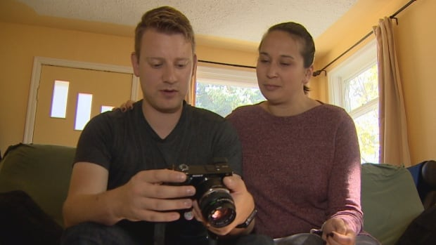 Stefan Strangman, left, and Nicole Misener, right, look at pictures taken in the aftermath of a magnitude 7.1 earthquake that hit Mexico City while they were on their honeymoon.