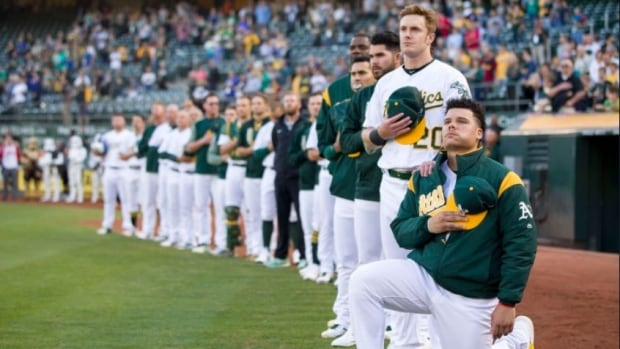 Bruce Maxwell, right, dropped to a knee just outside Oakland's dugout prior to Saturday evening's game.