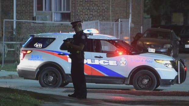 A Toronto police officer stands near the scene of a shooting on Gerrard Street East on Saturday night.