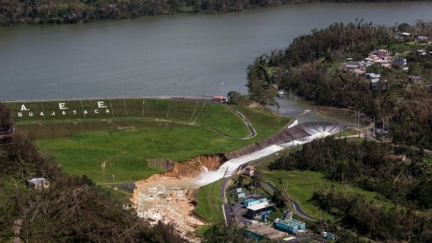 Water drains from the Guajataca Dam in Quebradillas, Puerto Rico, on Saturday. Fears that the dam could fail prompted the government to evacuate nearby residents.