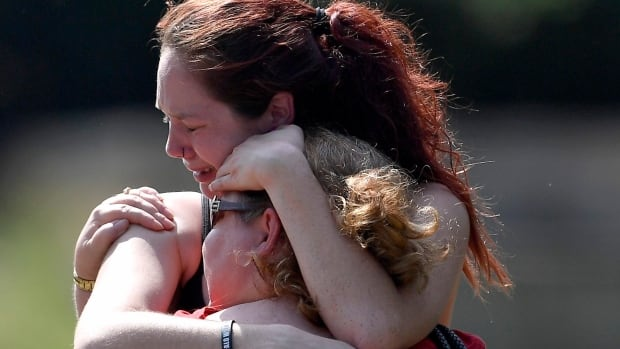 Kaitlyn Adams, a member of the Burnette Chapel Church of Christ, hugs another church member at the scene after a deadly shooting at the church on Sunday in Antioch, Tenn.